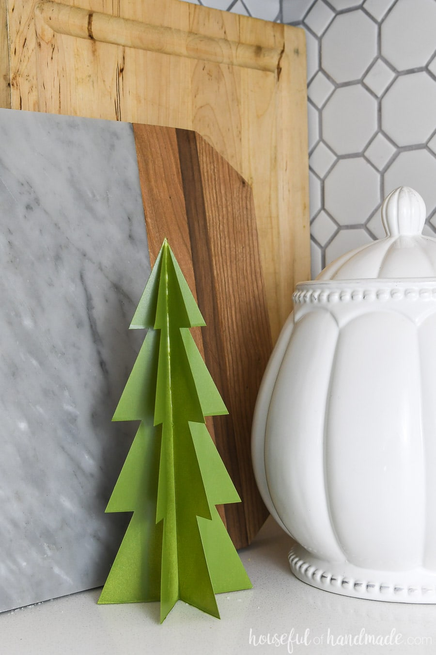 Green paper Christmas tree decor on the counter in the kitchen.