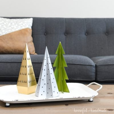 Tray of paper Christmas trees on a coffee table with a gray sofa in the background.