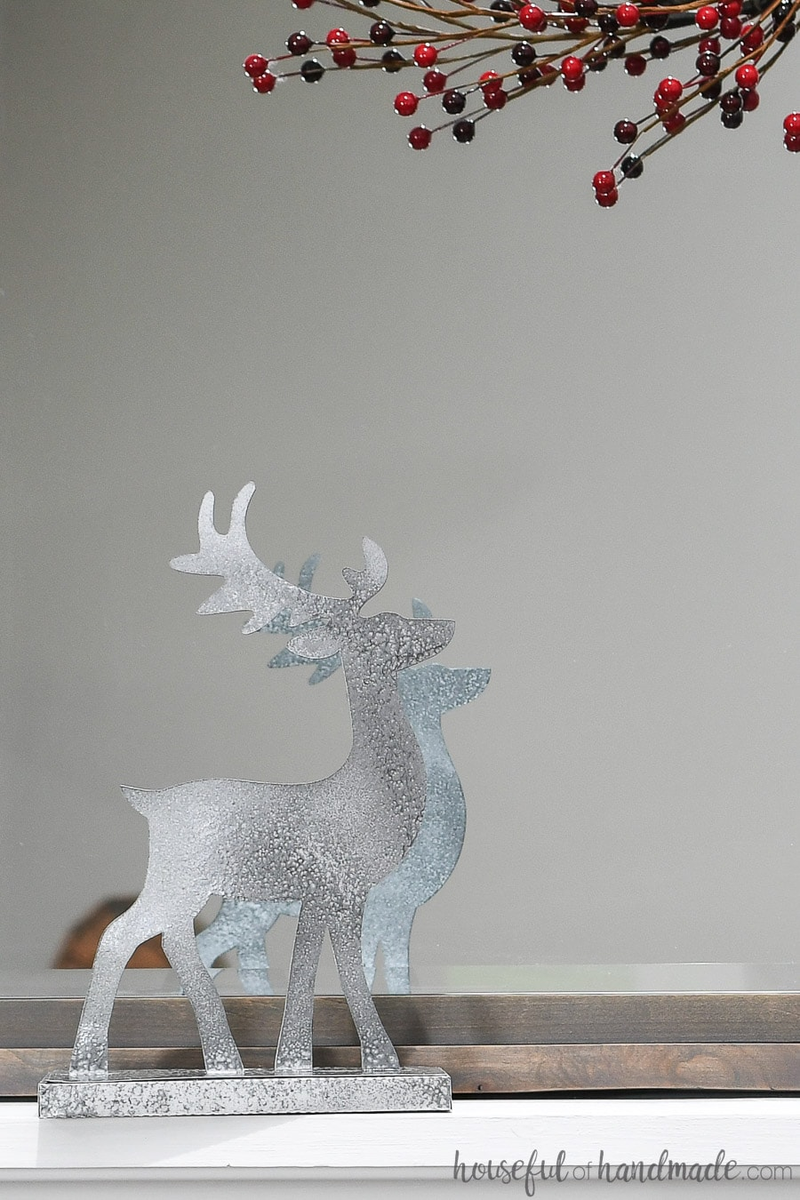 Close up of the Christmas reindeer decorations on the mantel in front of a mirror.