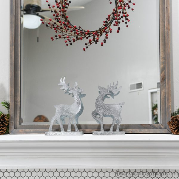 Two Christmas reindeer decorations on the mantel in front of the mirror with classic mantel decor.