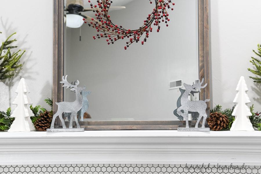 Christmas mantel decorated with DIY reindeer figurines.