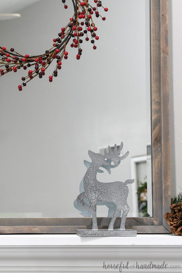One paper reindeer decorations in front of a mirror under a red berry wreath.