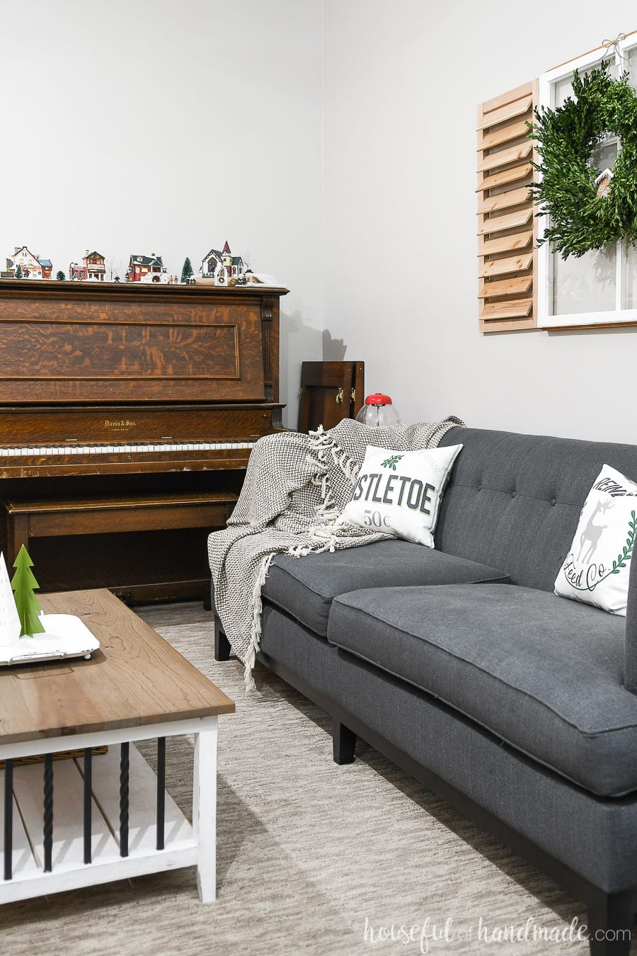 View of the sofa and piano decorated with classic Christmas decor.