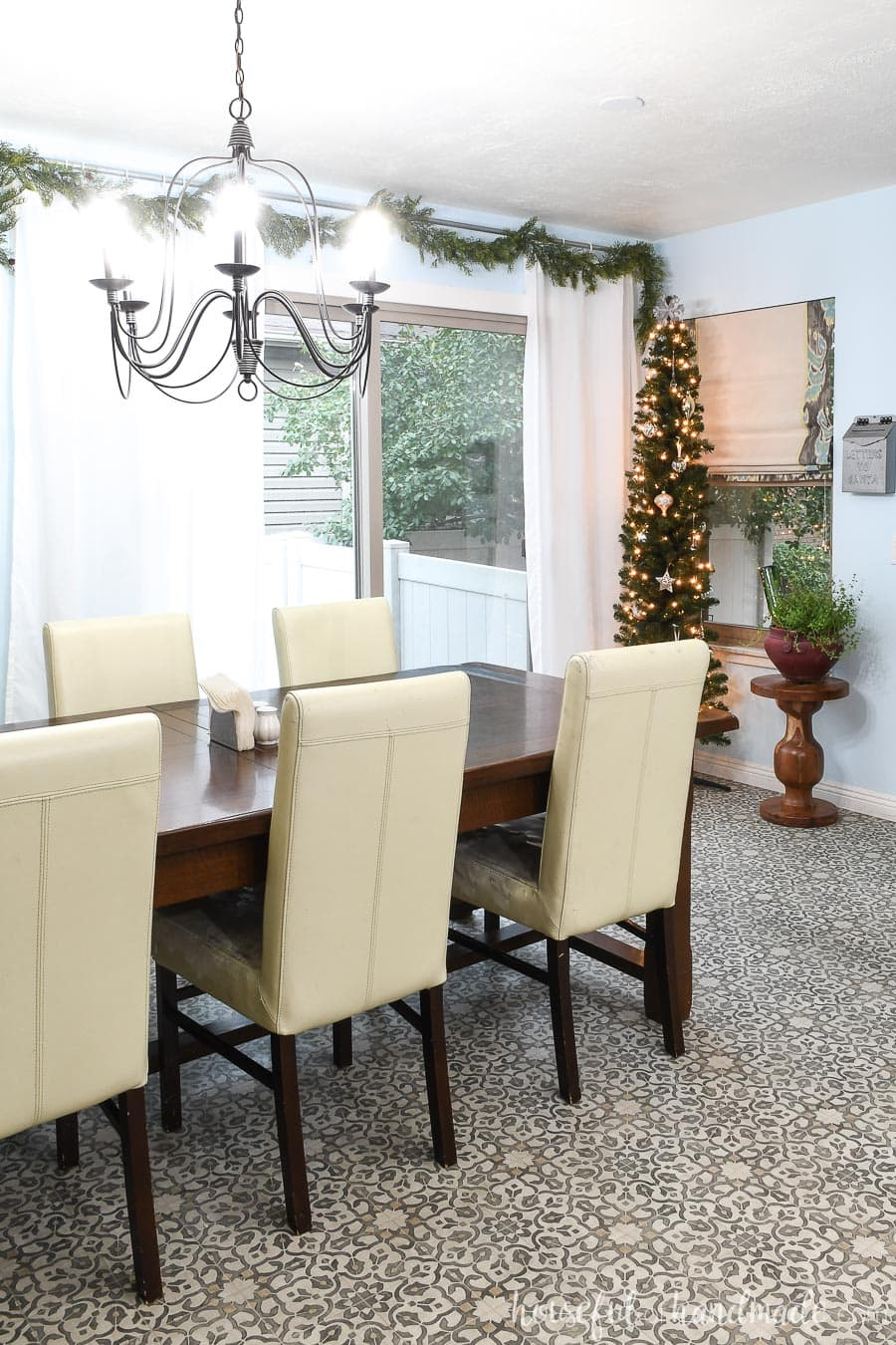 Dining room with a pencil Christmas tree in the corner and garland on the sliding door as part of the classic Christmas home tour.