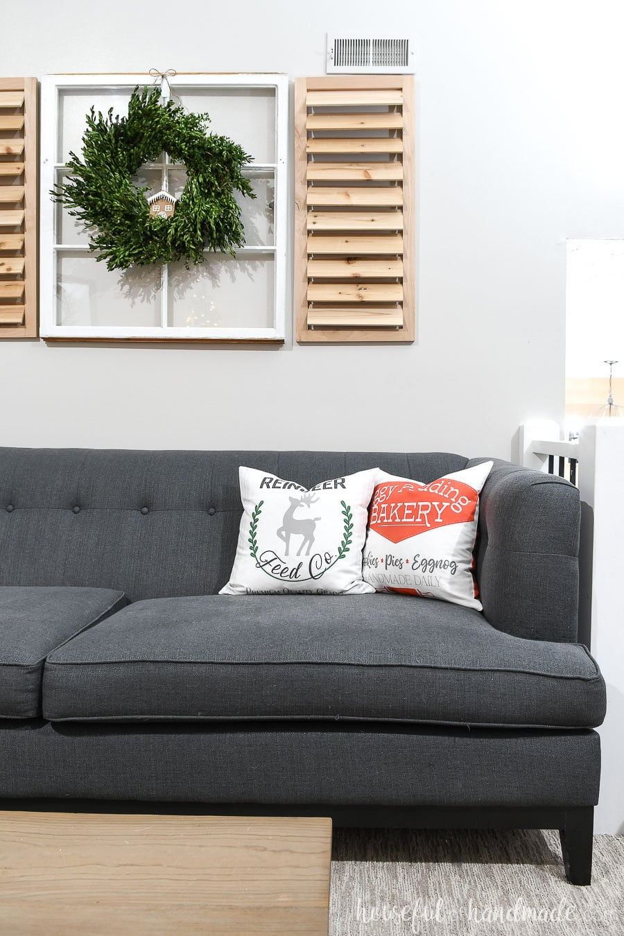 Gray sofa with Reindeer Feed Company and Figgy Pudding Bakery pillow on it.