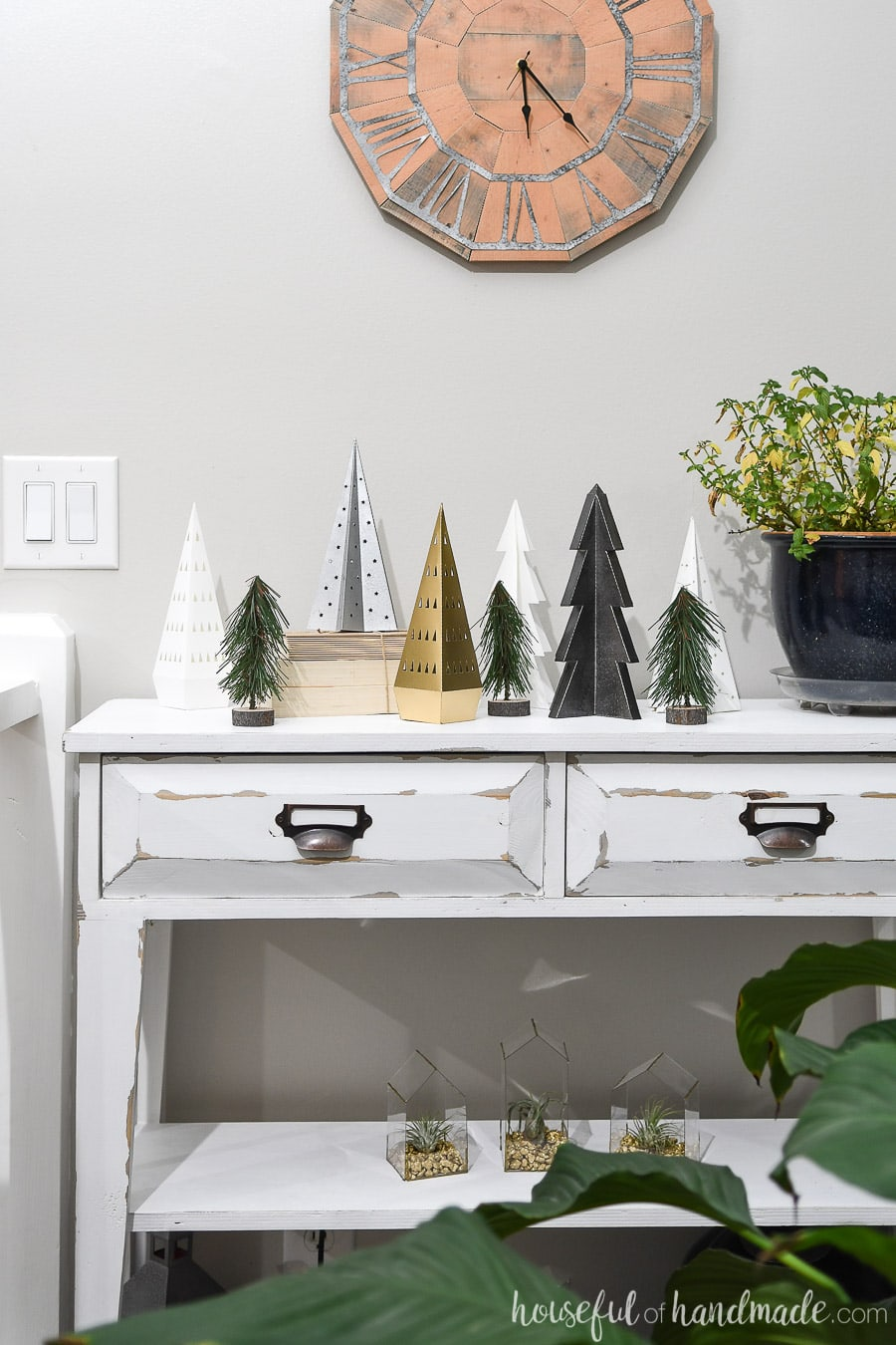 Small console table with a variety of paper Christmas trees on top of it.