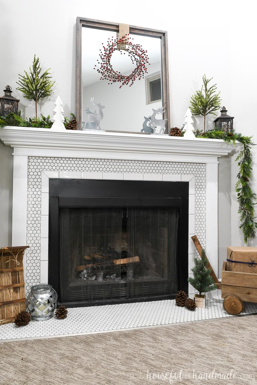 White fireplace surround with mantel decorated for Christmas with classic Christmas decorations.