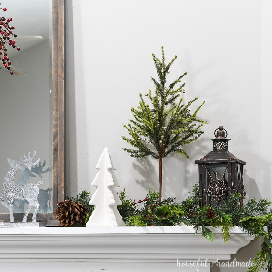 Garland tucked behind the mirror to give the classic Christmas mantel a slightly modern flair.