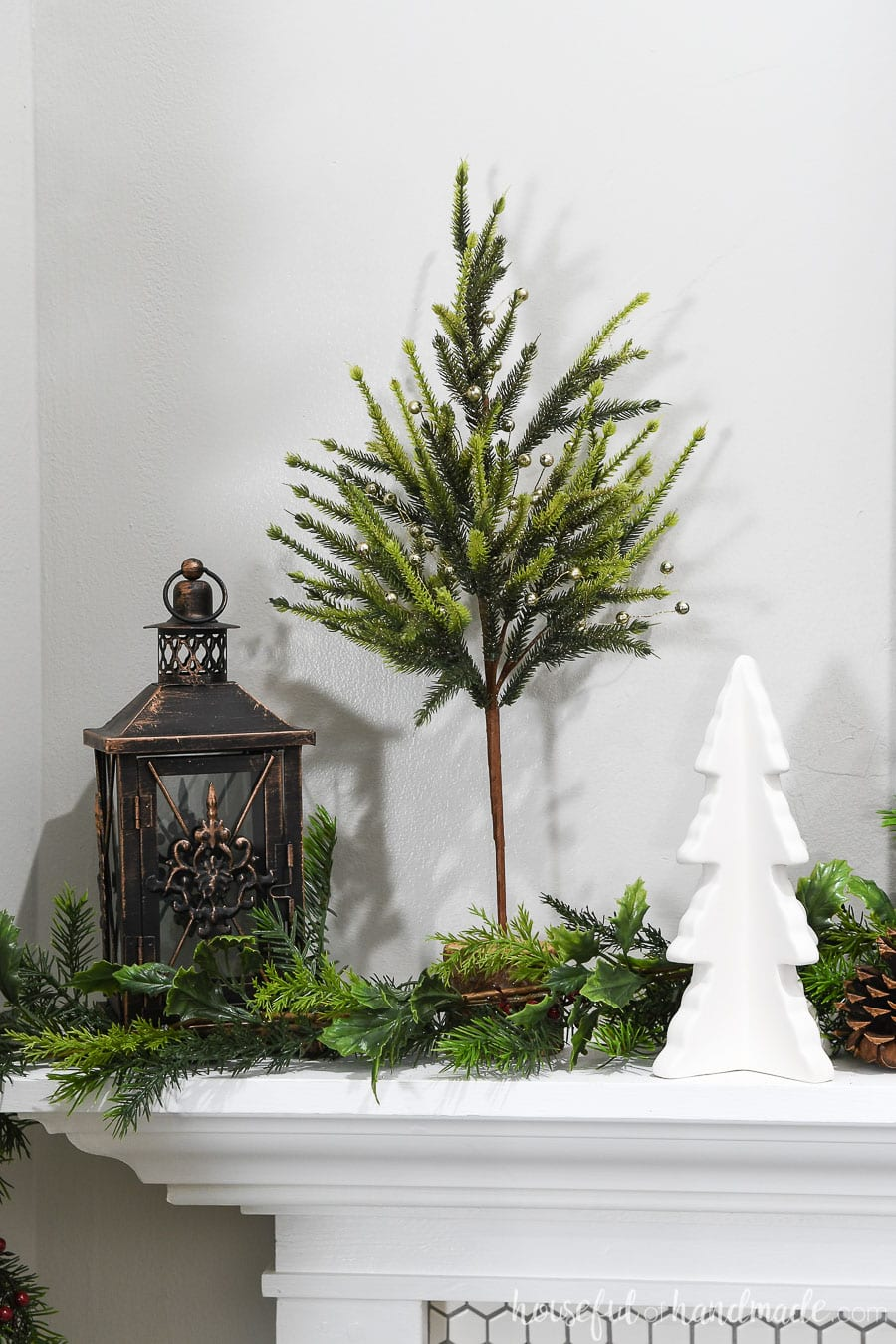 Quirky Christmas trees and lantern decorating a mantel for Christmas.