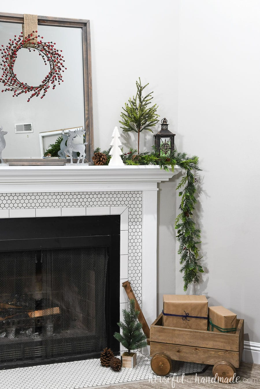 Side view of the mantel all decorated for Christmas with a wood wagon, mini Christmas trees, garland, and reindeer.
