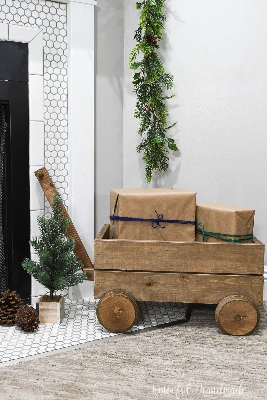 Decorative wood wagon with presents on the side of the classic Christmas mantel.
