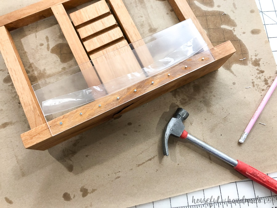 Step 9: Attach the plexiglass to the cookbook stand with a hammer and nails.