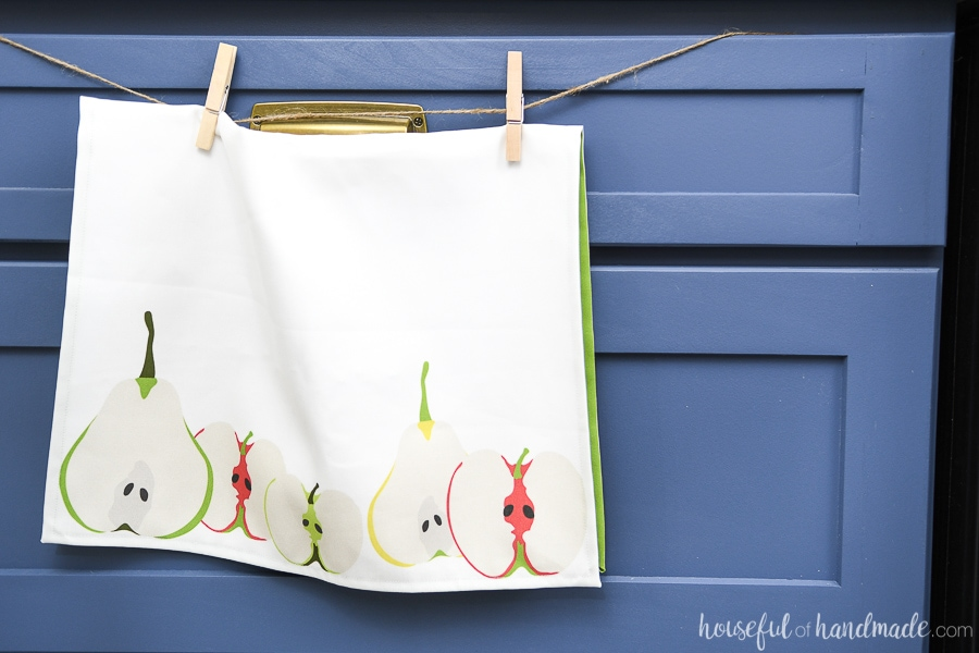 Custom printed tea towel with apple and pear design hanging over a blue kitchen cabinet drawer.
