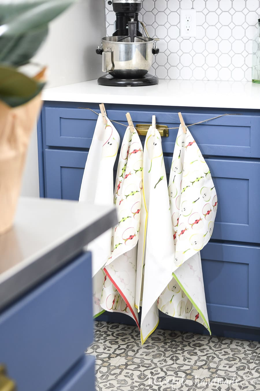 Decorative tea towels with apple and pear designs on it hanging on twine over blue cabinets.