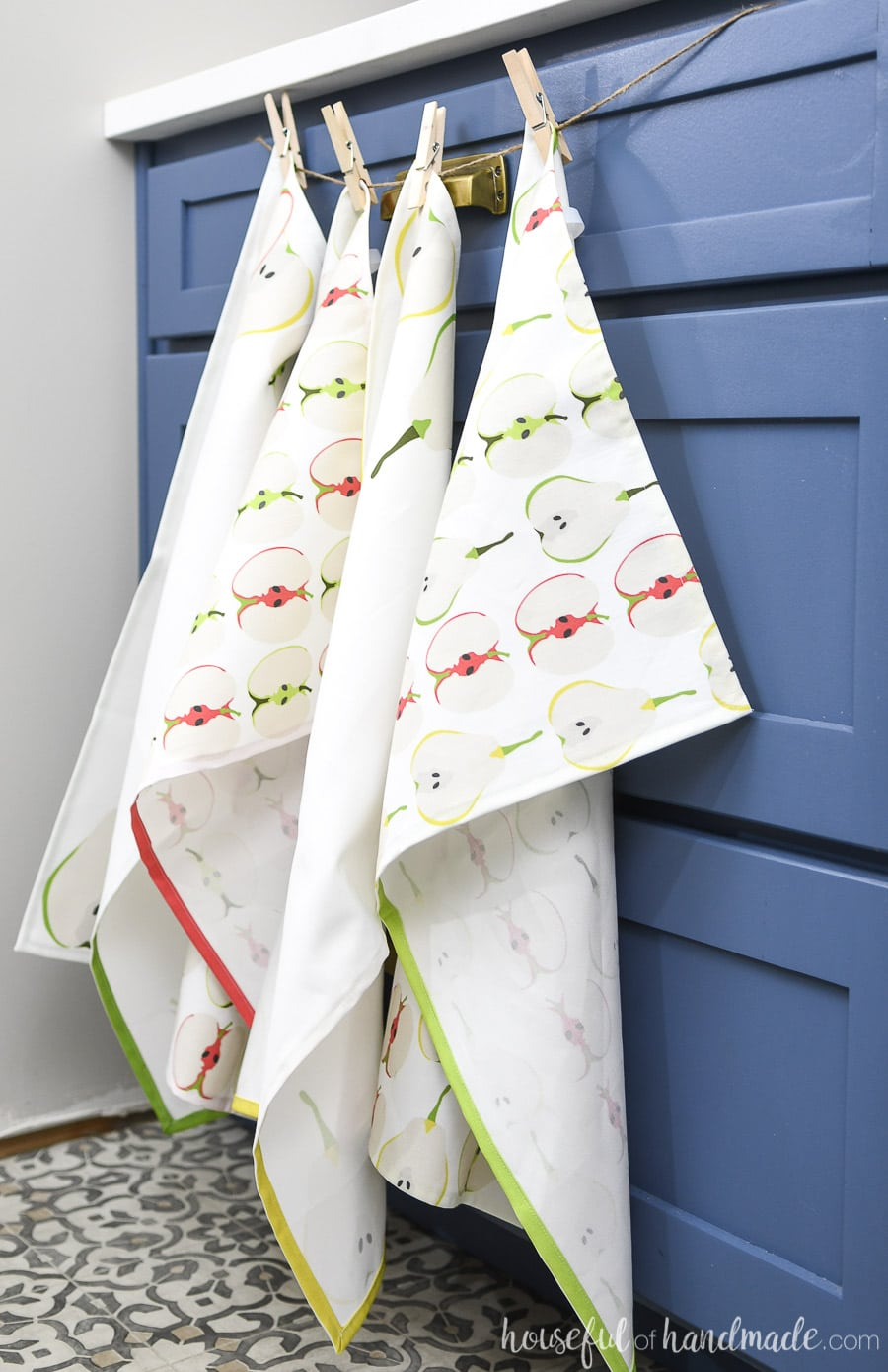 Four decorative fall tea towels hanging over kitchen cabinets.