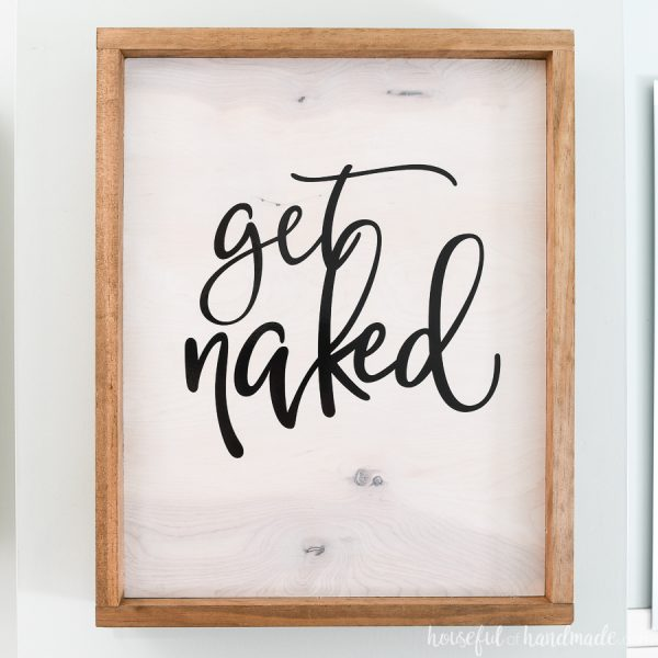 Get Naked wood sign is the front of the hidden DIY wall jewelry organizer.
