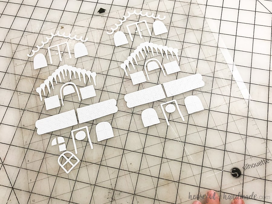 Paper gingerbread house decorations cut out of white cardstock.