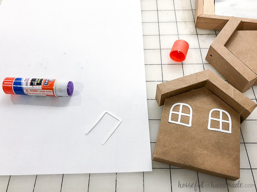 Glueing the decorations on the paper gingerbread houses with a glue stick.