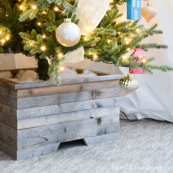 Square photo of the reclaimed wood Christmas tree stand cover with the tree inside.