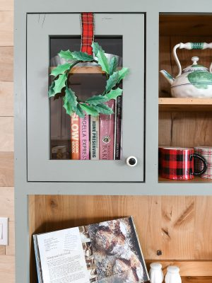 Gray hutch with natural wood interior and paper Christmas wreath hanging on the door.