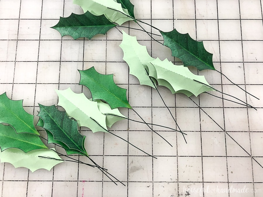 Step 2 of making paper Christmas wreaths: glue a piece of floral wire to the back of each leaf.