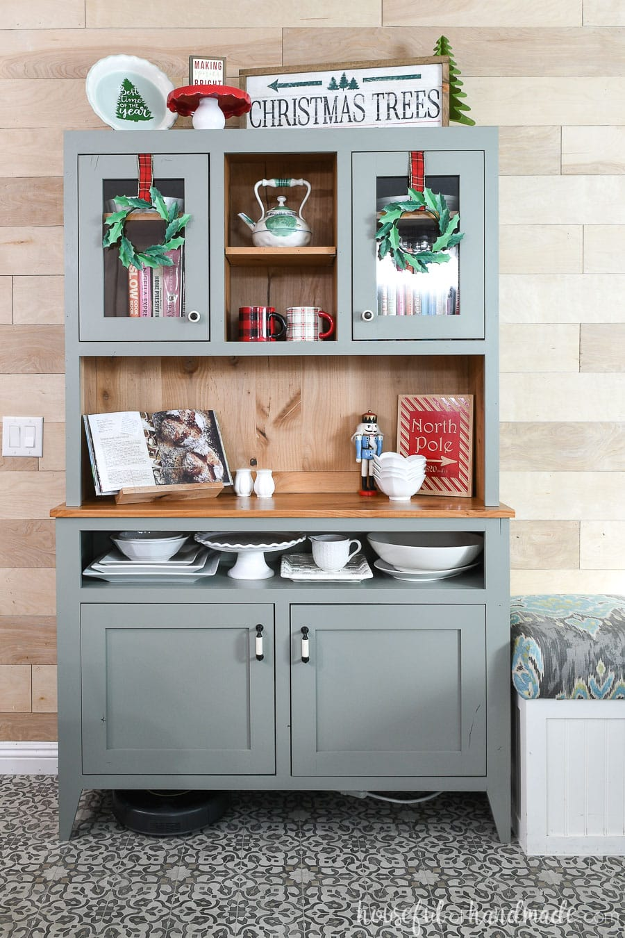 Rustic modern hutch decorated with Christmas decor and paper holly wreaths hanging on the hutch doors.