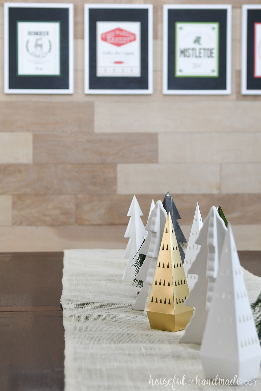 Dining room table filled with a variety of paper Christmas trees and framed printable Christmas signs in the background.