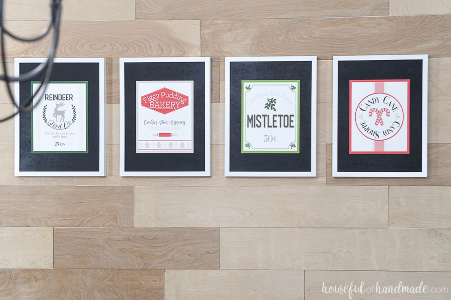 View of the 4 printable Christmas signs in white picture frames with black mats.