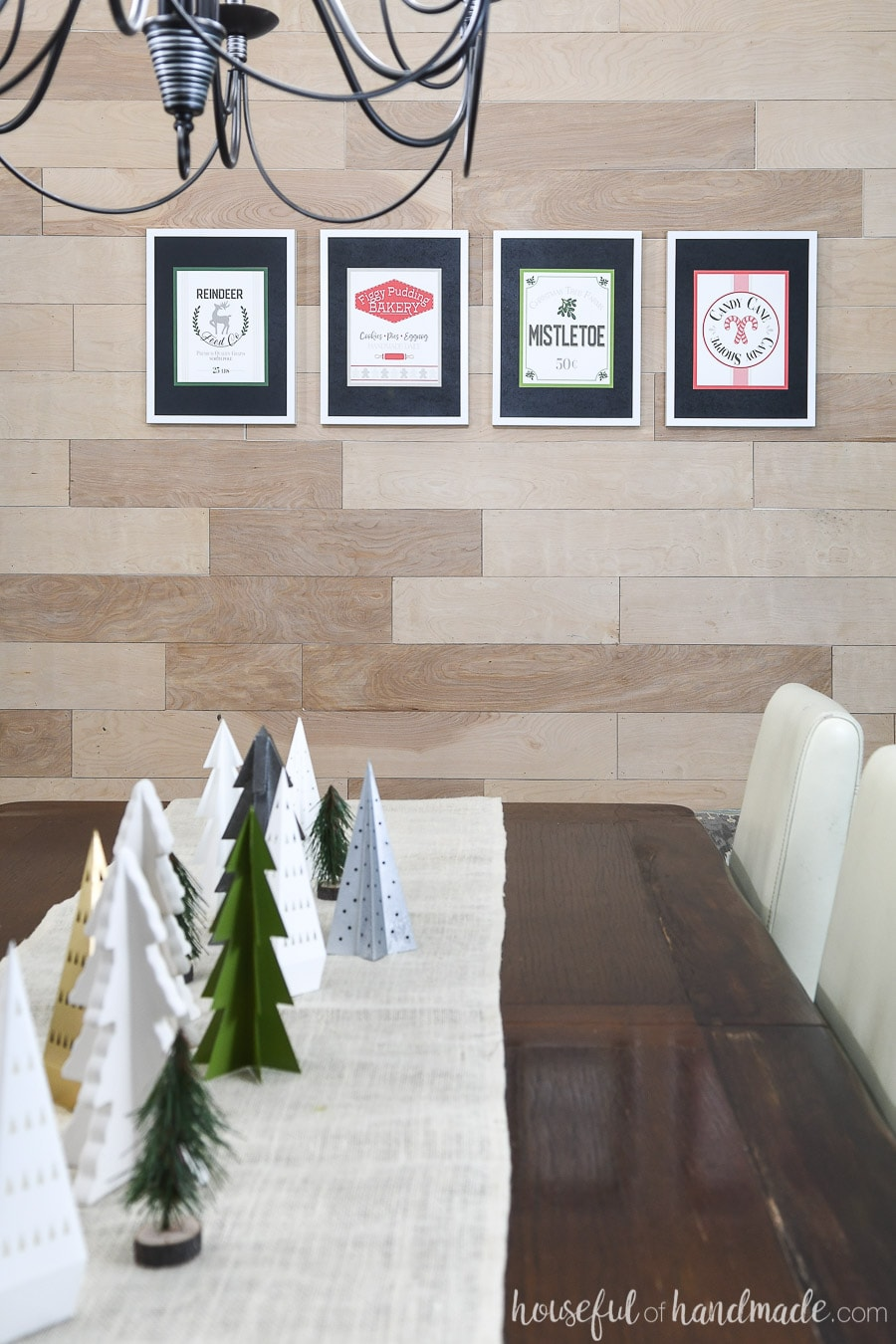 Four printable Christmas signs hanging in white frames on a wood wall.