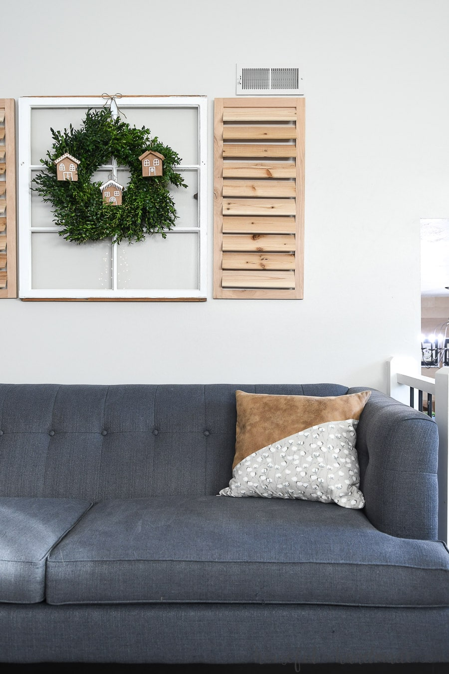 Living room with gray-blue couch and boxwood wreath hanging on a vintage mirror with shutter decor and paper Christmas ornaments.