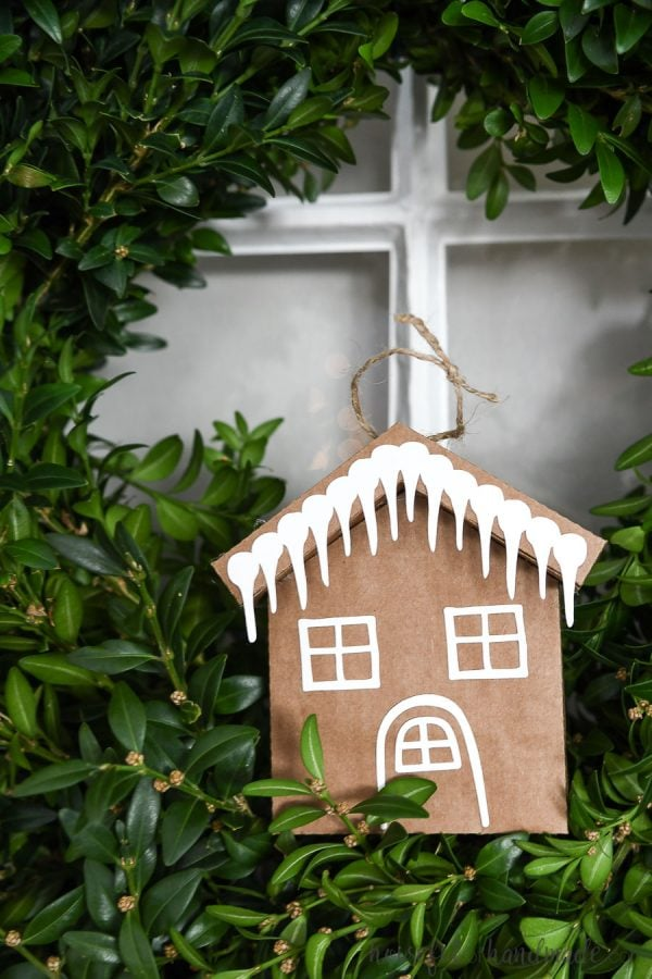 Paper gingerbread house ornament with icicle decoration.