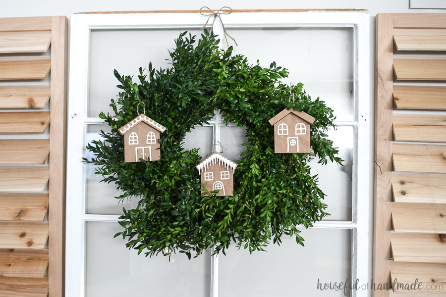 Boxwood wreath on a vintage window with gingerbread house paper Christmas ornaments hanging on it.
