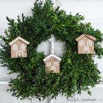 Square photo of gingerbread house paper Christmas ornaments hanging on a wreath.