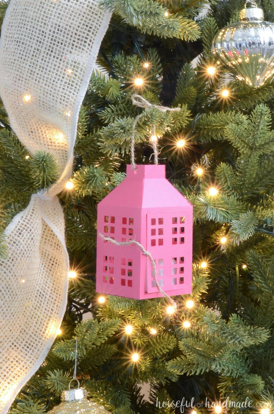 Rustic pink paper lantern Christmas ornament hanging on the Christmas tree.