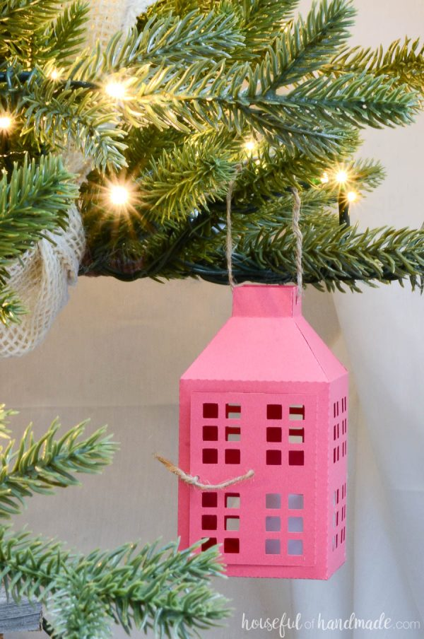 Paper Christmas tree ornament in the shape of a farmhouse lantern hanging on the branches of a Christmas tree.