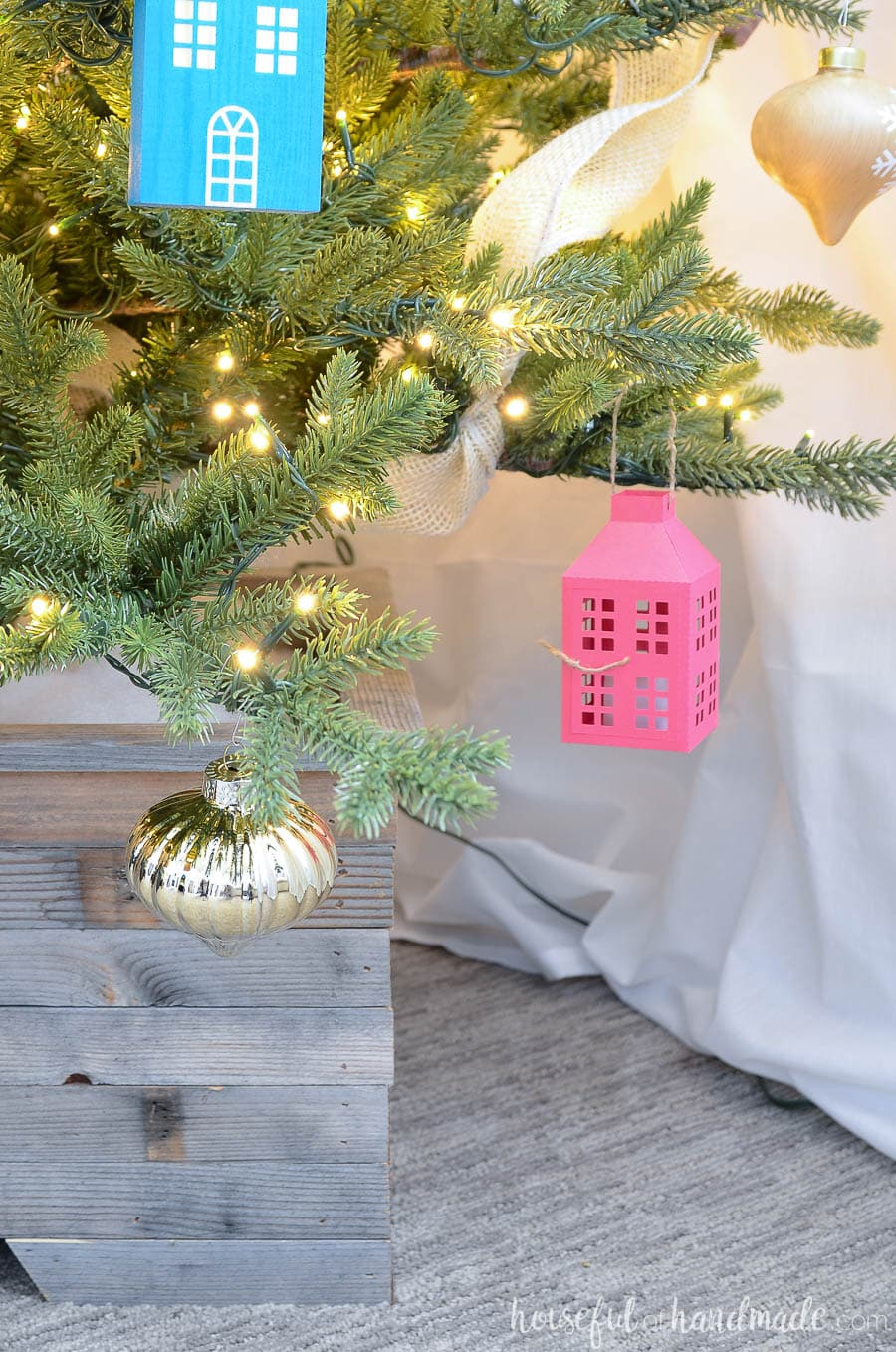 Christmas tree decorated with paper lantern Christmas ornament and wood house.