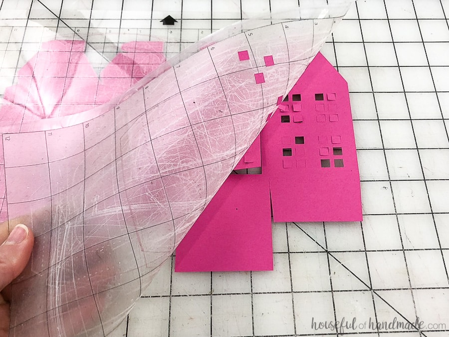 Pulling the cutting mat off the paper lantern to prevent rolling.