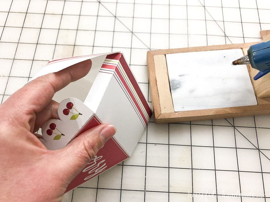 Hand holding the leftover pie box and glueing the side flaps to finish the box.