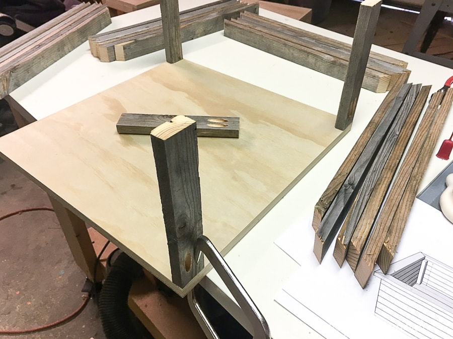 Attaching 1x2 support pieces of the wood Christmas tree stand to the plywood base.