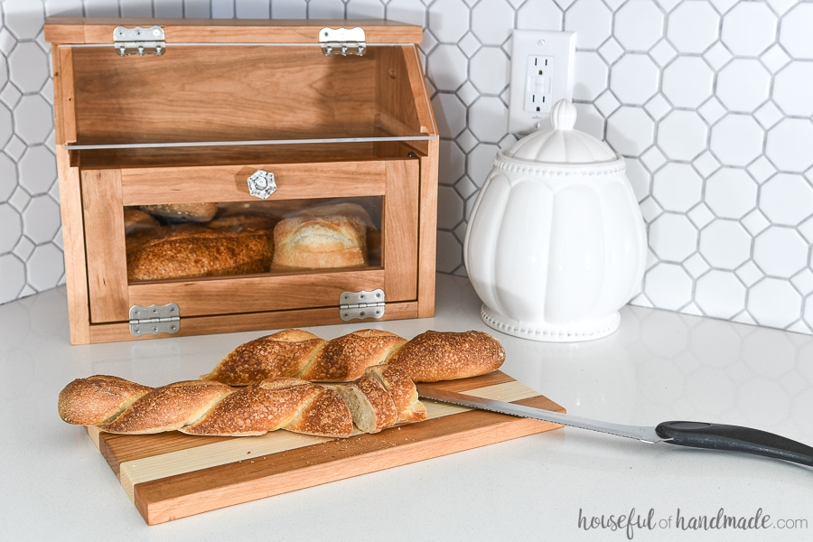 DIY bread box with pull out cutting board shelf with baguette on it.