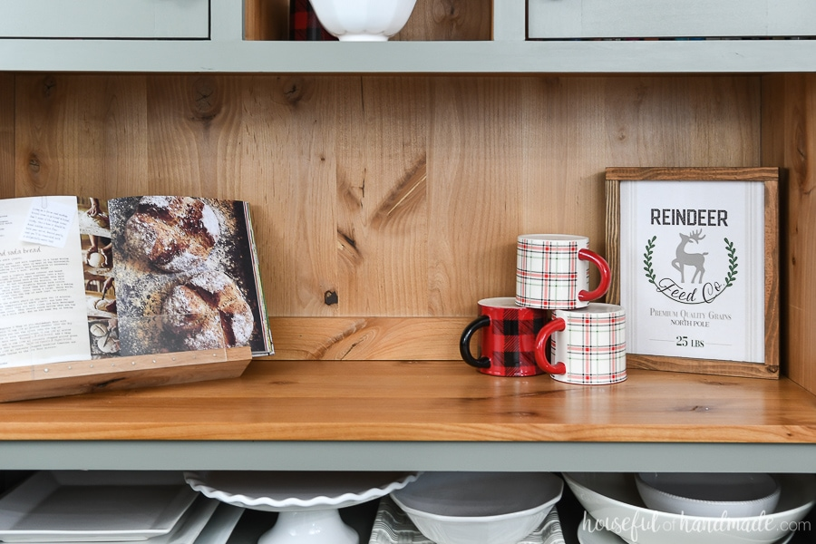 Easy DIY wood sign on the shelf of a hutch decorated for Christmas.