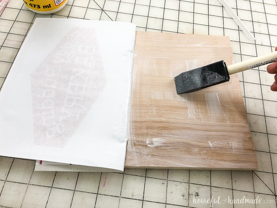 Attaching the printed art to the plywood DIY wood signs.