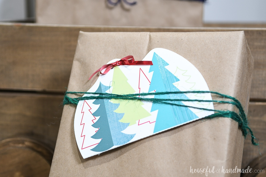 Printable Christmas gift card holder tucked into twine on the front of a present wrapped in brown packing paper.