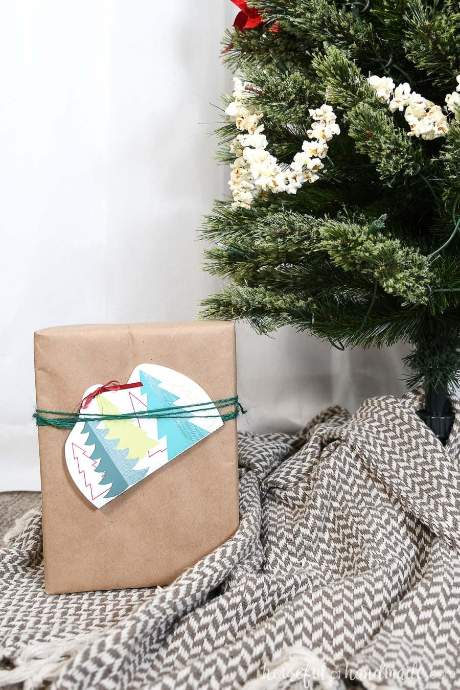 Christmas present wrapped under the tree with a gift card attached in a printable gift card holder.