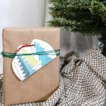 Printable Christmas gift card holder tied to a present under the tree.