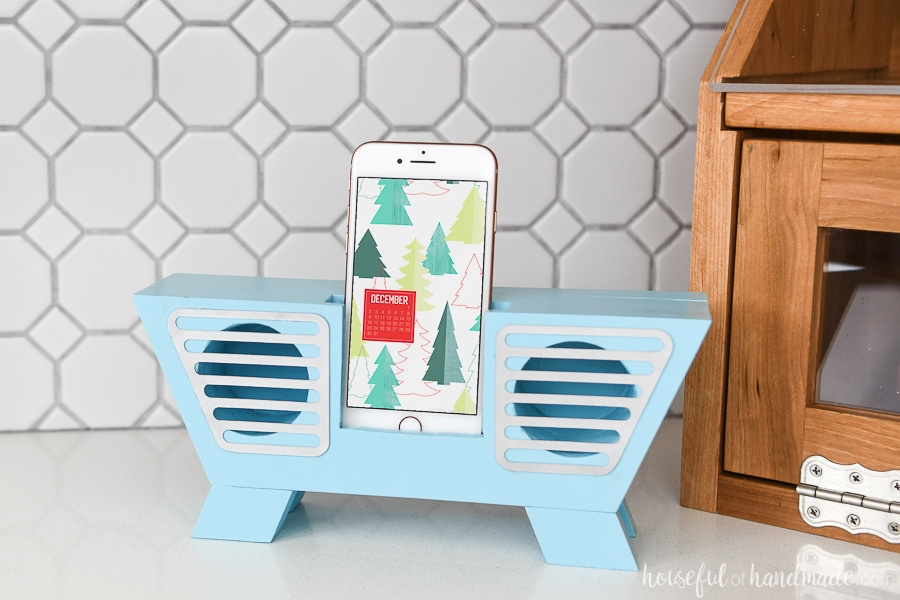 Blue painted retro wooden speaker for phone with an iPhone inside.