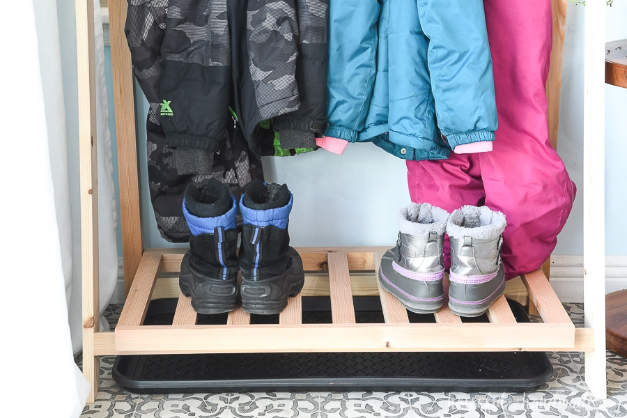 Close up of the bottom shelf of the fold-up storage shelves with snow boots on it and a drip tray below to catch melting snow.