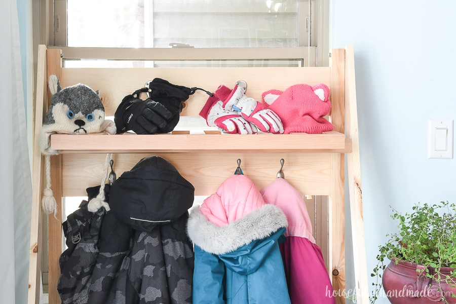 The top shelf of the collapsible storage rack with hats and gloves on it.
