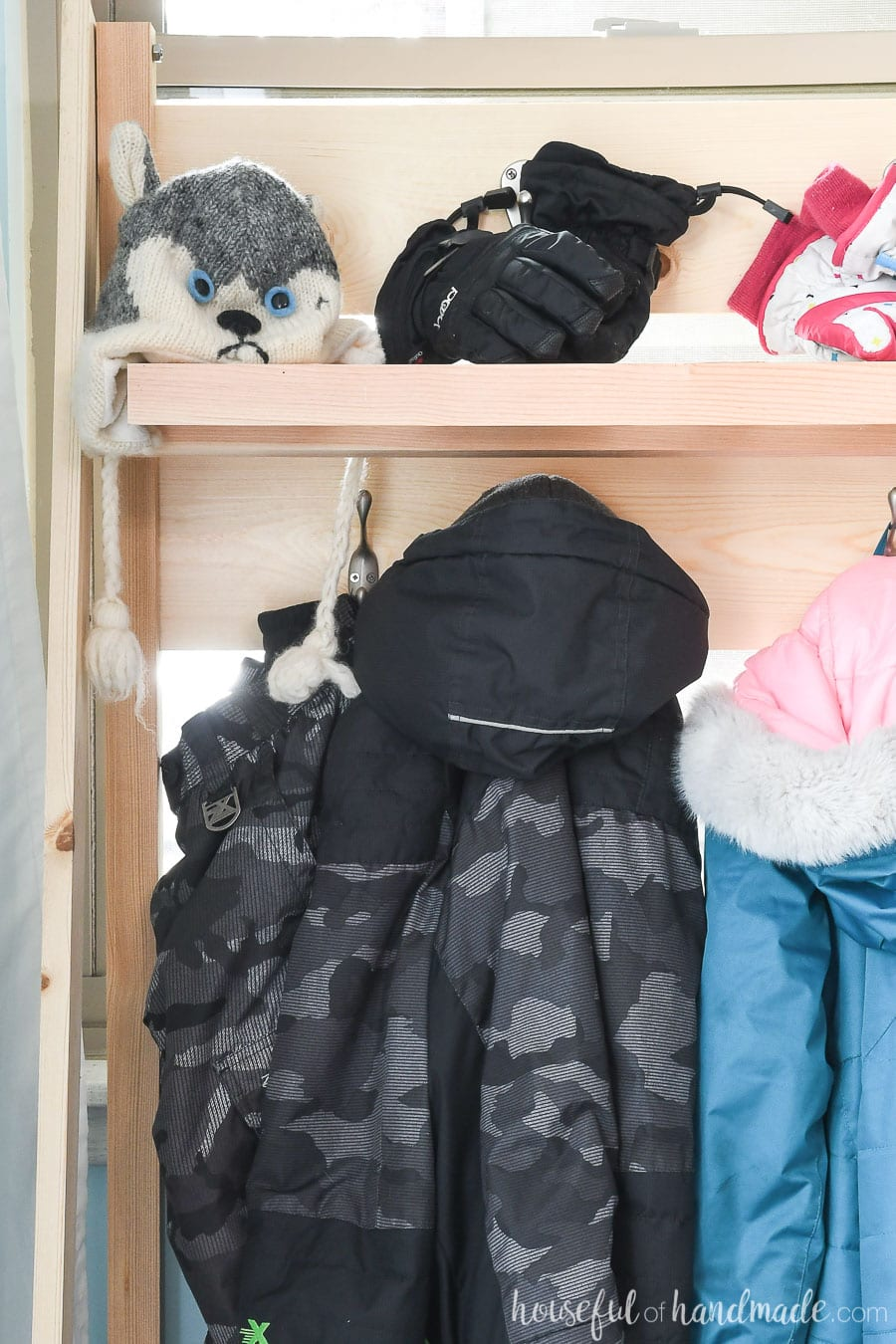 Close up of the coats hanging on the collapsible storage shelves in the mudroom.