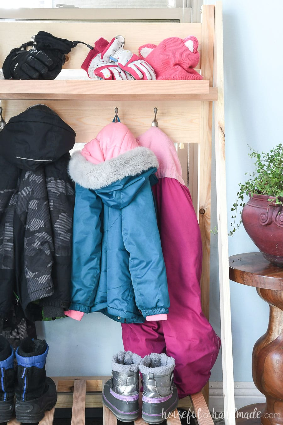 View of the fold-away mudroom shelves with coats and winter gear hanging on it.
